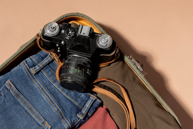 Bagagli aperti con vestiti piegati e macchina fotografica
