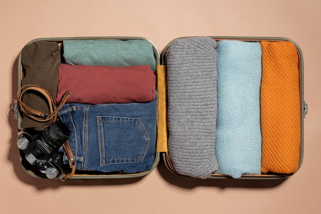 Opened luggage with clothes folded and camera