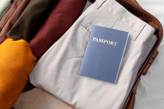 접힌 옷과 여권이있는 개봉 된 수하물