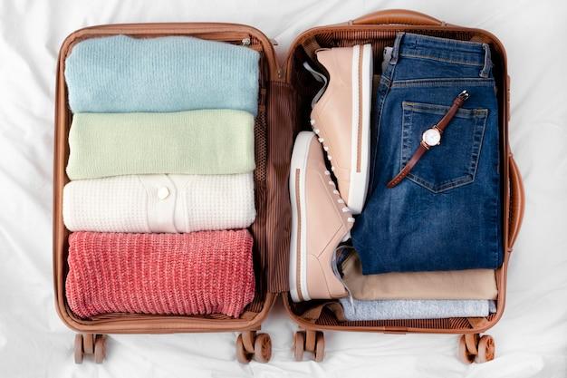 Открытый багаж со сложенной одеждой и обувью