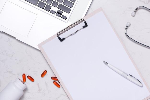 Открыл флакон с лекарством и разлил капсулы на столе с чистым листом бумаги и ноутбуком.