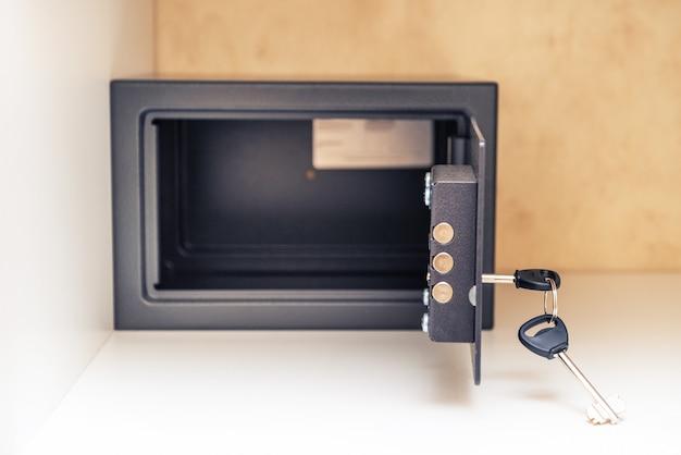Раскрытый металлический сейф с ключом и открытая дверь в гостиничном номере, внутри шкафа