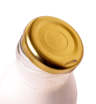 Opened milk glass bottle with metal lid on the white surface