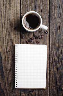 나무 테이블에 열린 노트북과 커피