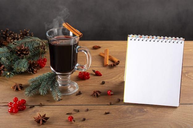 開いたノート、モミの枝、ホットワイン、スパイス、コーンのグラス
