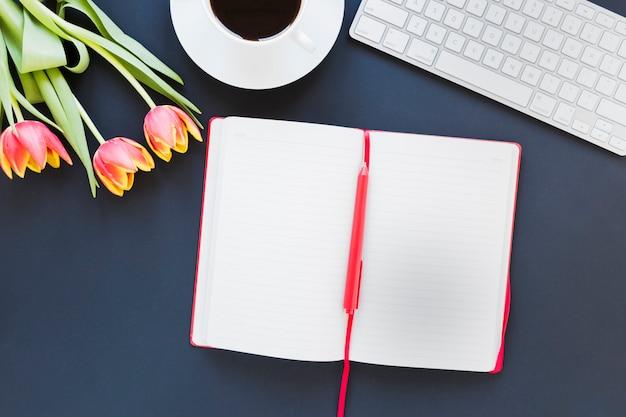 コーヒーカップとキーボード付きの机の上のチューリップの近くのノートブックを開く