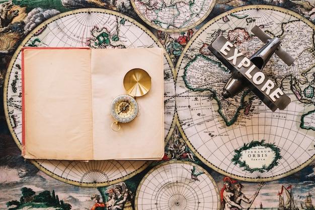 Открытая записная книжка возле компаса и самолета