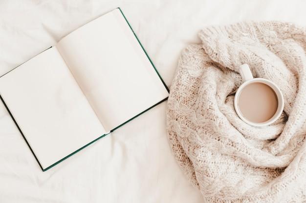 Открытая записная книжка рядом с горячим напитком в плед