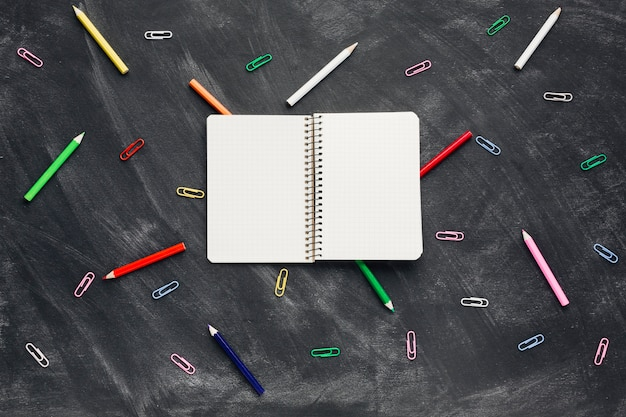 Opened notebook near pencils and paper clips