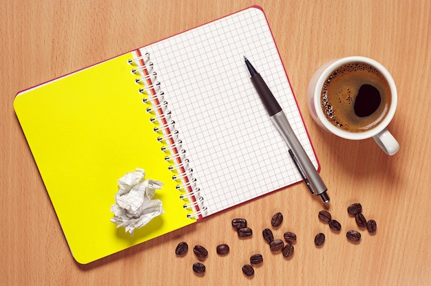Opened notebook, pen and cup of hot coffee on desk, top view
