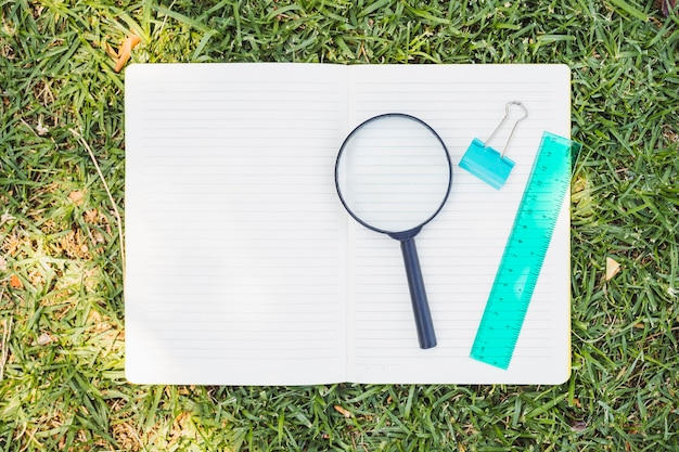 Opened notebook with magnifier on grass