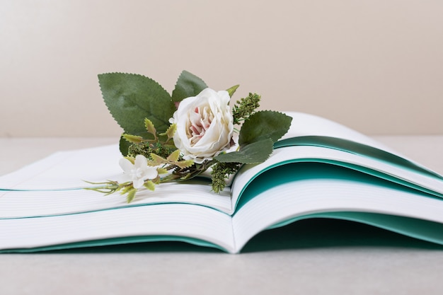 Открыл блокноты с поддельной розой на бежевом фоне. фото высокого качества