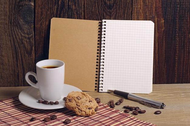 오래된 나무 테이블에 초콜릿 쿠키가 있는 메모장과 커피 컵을 열었습니다.