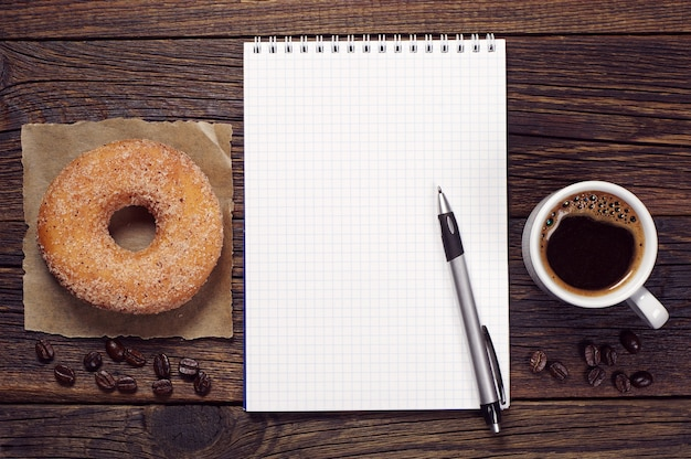 Opened notepad and cup of coffee with donut on dark wooden table, top view