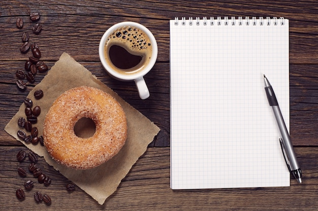 Opened notepad and cup of coffee with donut on vintage wooden table, top view