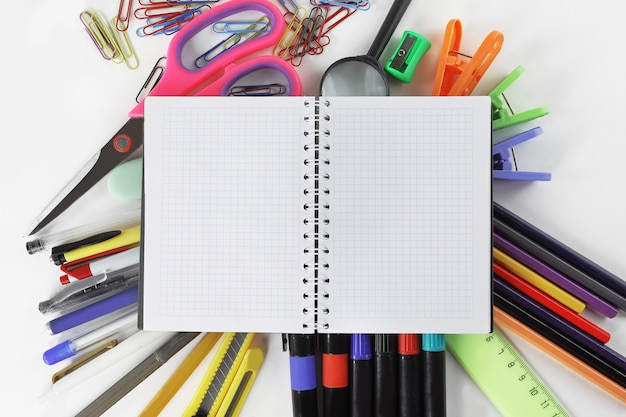 Opened notepad on office supplies on white background