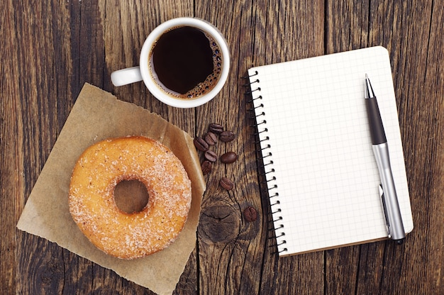 Opened notepad with cup of coffee and donut