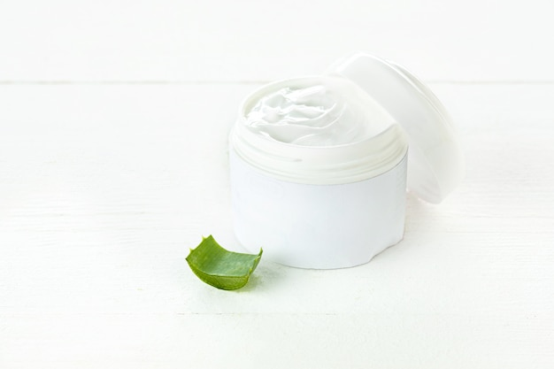 Opened plastic container with cream and aloe