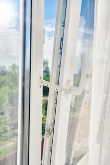 Opened plastic window frame. plastic window installation. apartment ventilation through window. sunny morning outside the white plastic window.