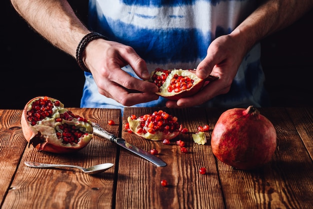Opened pomegranate fruit in hands and other pieces with knife and spoon on the table