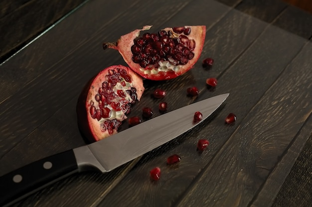 Opened pomegranate on a wooden table. sliced pomegranate and kitchen knife.