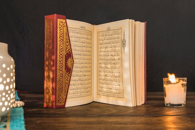 Opened quran between lantern and candle