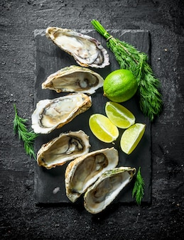 Opened raw oysters on black stone board with lime and dill on black rustic table