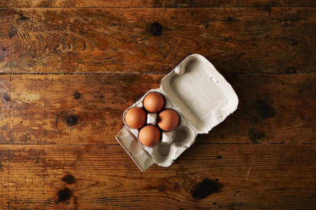 Opened recyclable egg carton for six eggs containing four big brown eggs on a rough rustic brown wooden table