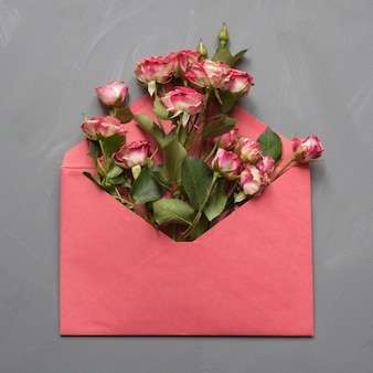 Opened red envelope with pink roses on gray