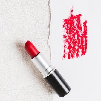 Opened red lipstick tube and smudge on paper sheet
