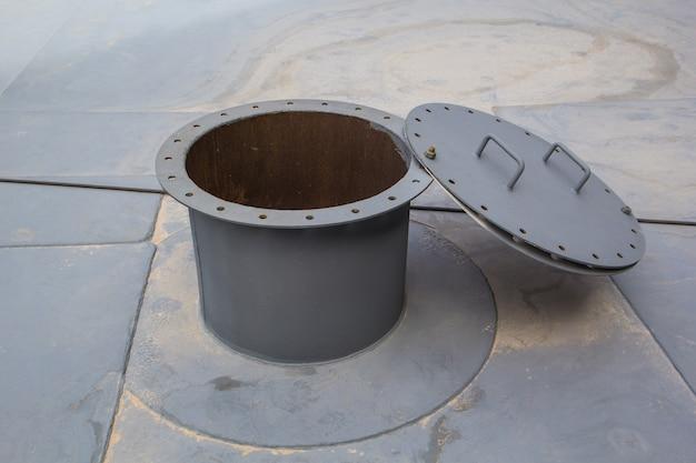 흰색 연료 탱크 지붕 데크 저장 탱크 밀폐 공간에 녹슨 맨홀을 열었습니다.