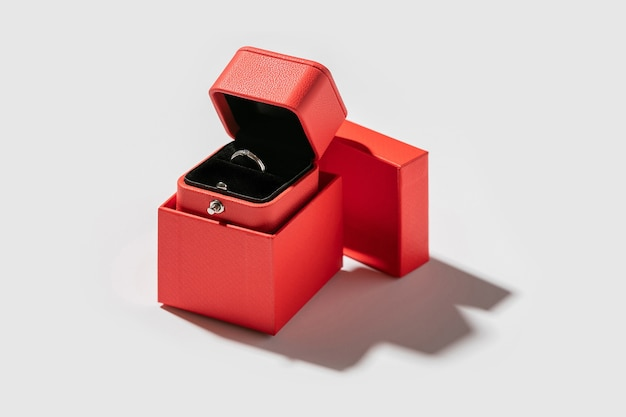 Opened small present box made of red paper, with with engagement ring inside of it