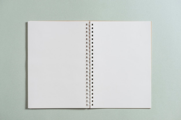 Opened spiral blank book on colored background