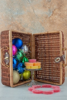 Opened suitcase full of colorful christmas balls and marmalade on marble background. high quality photo