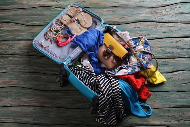 Открытый чемодан с мятой одеждой. сандалии и браслеты в багажной сумке. не разбивайте солнцезащитные очки. готов к путешествию.