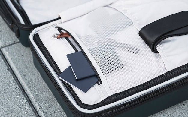 Opened suitcase with passports watch and tie