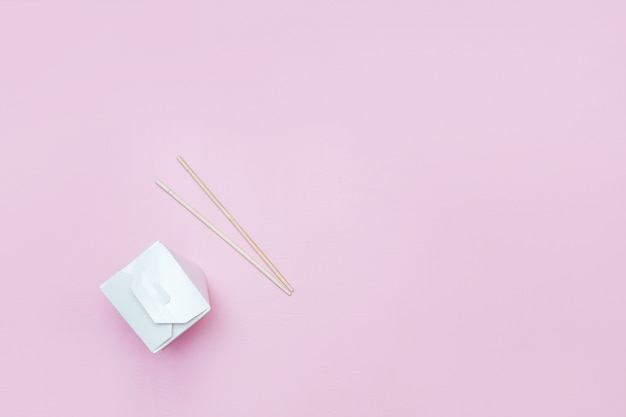Opened takeaway box for chinese noodles presented with chopsticks, on pink background