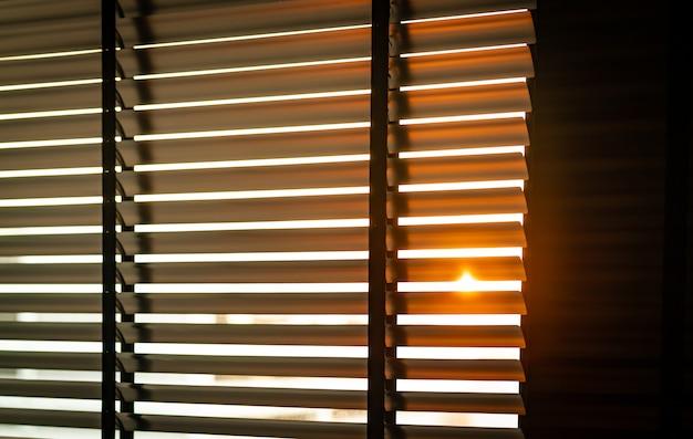 午前中に日光でベネチアンプラスチックブラインドを開きました。ブラインド付きの白いプラスチック窓。ウィンドウ水平ブラインド付きのリビングルームのインテリアデザイン。