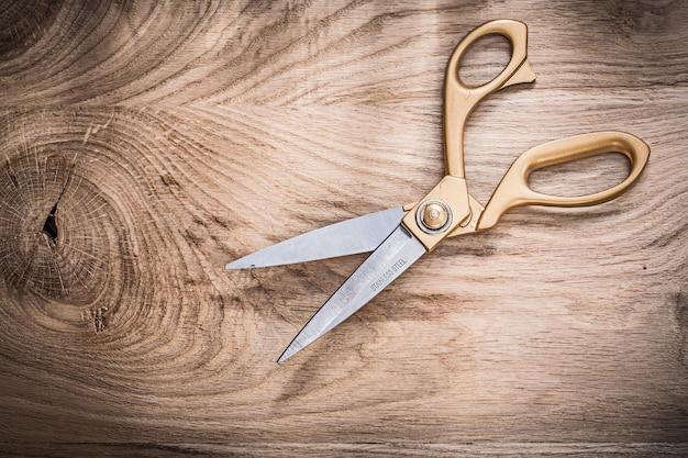 Opened vintage golden scissors on wooden board