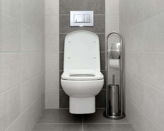 Открыт белый унитаз в современной ванной комнате