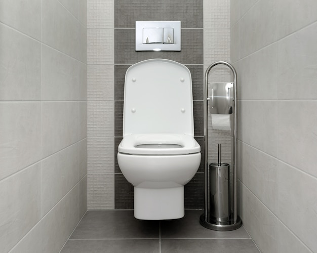 Opened white toilet bowl in modern bathroom
