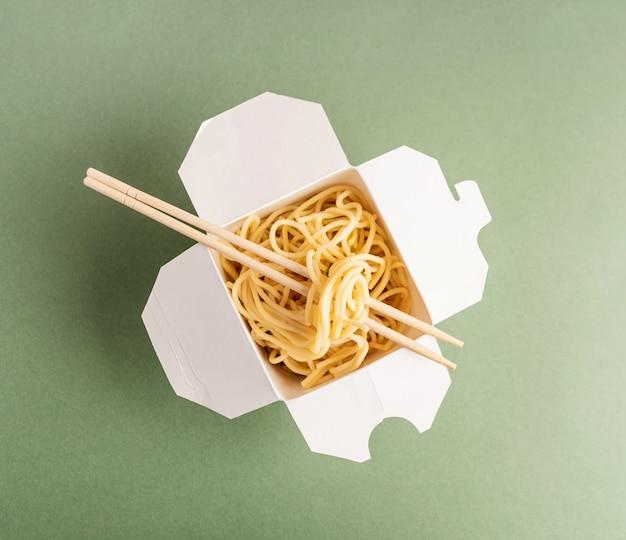 Открытая бумажная коробка wok с лапшой и палочками для еды, вид сверху, лежала на зеленом фоне