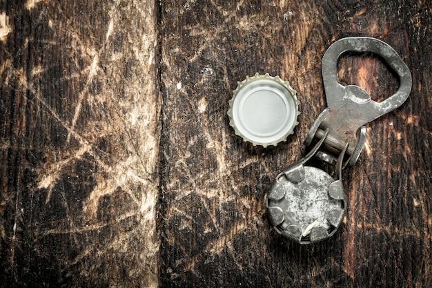 Открывалка и пробка для пивных бутылок на деревянном фоне