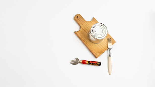 Opener, fork and metal tin on brown wooden cutting board on white background