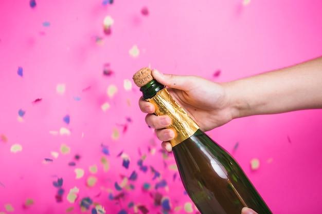 パーティーでシャンパンのボトルを開く