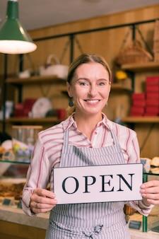 빵집을 여는 중입니다. 아침에 줄무늬 앞치마 여는 빵집을 입고 쾌활한 사업가 웃고