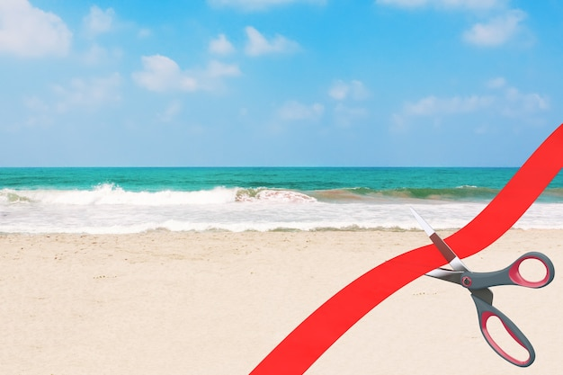 Opening beach tourism after covid-19 quarantine concept. scissors cutting red ribbon in front of blue cloudy sky ocean or sea sand beach extreme closeup. 3d rendering