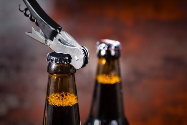 Открытие пивной бутылки металлическим открывалкой. концепция еды и напитков