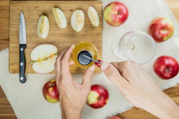 Раскрывающая бутылка яблочного напитка, вид сверху. точка зрения руки с консервный нож, готовит напиток из сидра на деревенский деревянный столик со спелыми яблоками