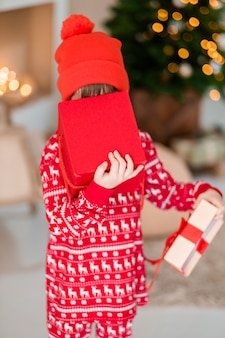 The opening of the child is present at the christmas tree at home boy in red pajamas